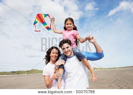 Familia divertirse volando cometa en vacaciones en la playa