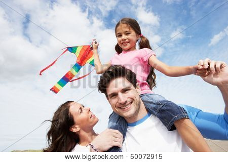 Father And Daughter Having Fun Flying Kite On Beach Holiday
