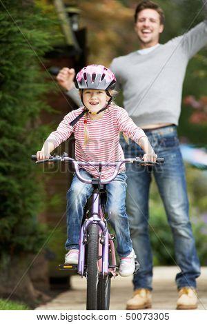 Father Teaching Daughter To Ride Bike In Garden