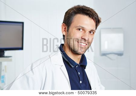 Portrait of a happy dentist in a white lab coat in dental practice