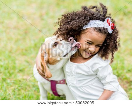 Happy girl with a dog licking her face