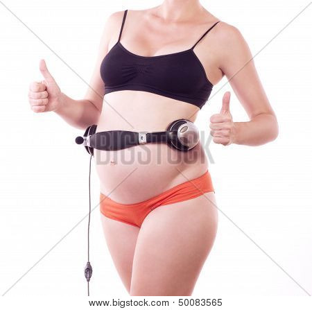 Young attractive pregnant woman listening music in headphones