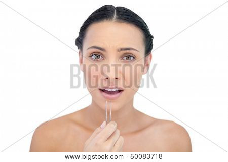 Astonished young model with tweezers on white background