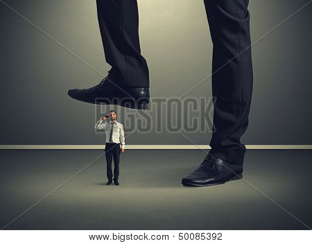 small desperate businessman with gun under big leg his boss
