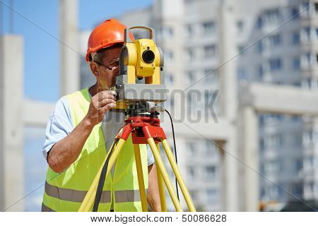 builder worker with theodolite transit equipment at construction site outdoors during surveyor work