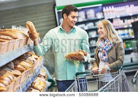 Man and woman choosing bread during shopping at bakery supermarket store