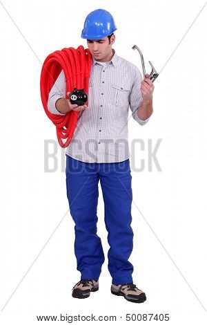 Plumber holding piggy-bank and tap