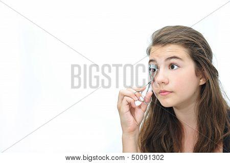 Nice teen girl holding an eyelash curler in her hand isolated on white background.
