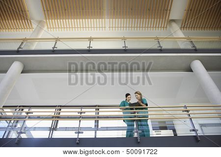 Low angle view of two female medical workers looking at chart on balcony