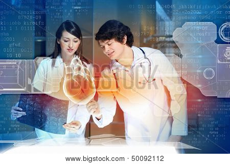 Image of two doctors cardiologist examining virtual heart