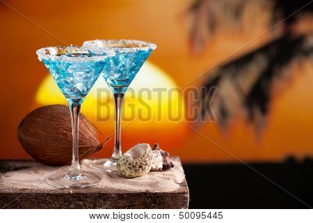 two blue cocktail on beach, sunset, palm tree, coconut