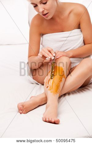 epilation: sitting woman remove with wax hair over white