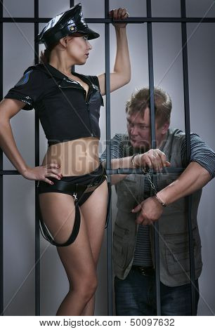 sexy lady police officer guards the offender in prison