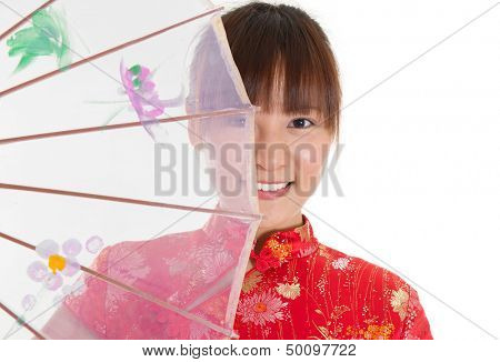 Asian woman with Chinese traditional dress cheongsam or qipao holding Chinese umbrella covering part of face. Chinese new year concept, female model isolated on white background.