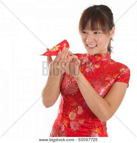 Asian woman with Chinese traditional dress cheongsam or qipao holding ang pow monetary gift, peeking into red packet. Chinese new year concept, female model isolated on white background.