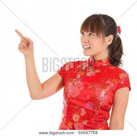 Pretty Asian woman with Chinese traditional dress cheongsam or qipao finger pointing at blank copy space. Chinese new year concept, female model isolated on white background.