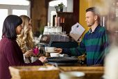 image of bartender  - Side view of bartender serving coffee to women in coffeeshop - JPG