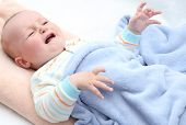 foto of scared baby  - little baby crying in bed on back - JPG