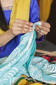 picture of dupatta  - Midsection of dressmaker working on a sari - JPG
