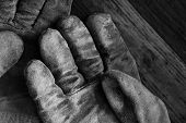 Artistic black and white image of well worn leather work gloves on wood background.  Low key still l