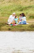 Grandparents And Grandchildren Having Picnic On Riverbank