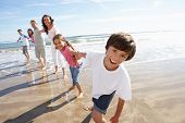 stock photo of 70-year-old  - Multi Generation Family Having Fun On Beach Holiday - JPG