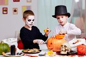 Photo of two eerie boys cutting holes in pumpkins at Halloween table