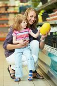 stock photo of melon  - Mother woman and little girl choosing melon during family shopping at fruit vegetable supermarket store - JPG