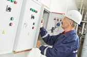 stock photo of fuse-box  - senior adult electrician builder engineer testing equipment in fuse box - JPG