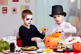 foto of antichrist  - Photo of two eerie boys cutting holes in pumpkins at Halloween table  - JPG