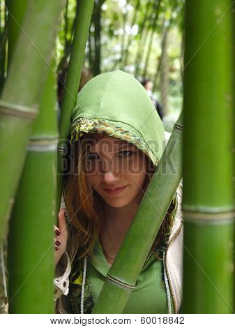 Young pretty woman walking in the park in the overgrowth of bamboo