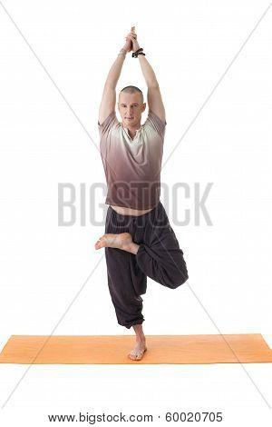 Smiling yogi posing standing on one leg
