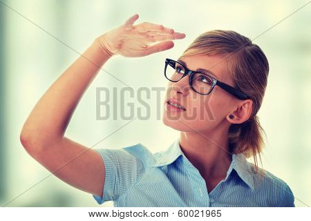 Portrait of a thoughtful young woman in blue shirt and glases (student, secretary or buisnesswoman)