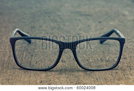 Geek eyeglasses laying on a grungy wooden background with retro filter effect