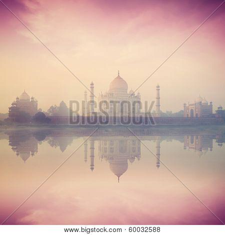 Vintage retro hipster style image of Taj Mahal on sunrise sunset reflection in Yamuna river panorama in fog, Indian Symbol - India travel background. Agra, Uttar Pradesh, India