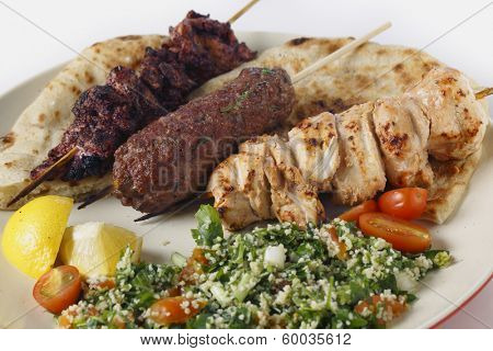 Various barbecued kebabs - kofta, chicken tawook and sumac chicken - with tabouleh and pitta bread; an Arab or Lebanese-style feast,