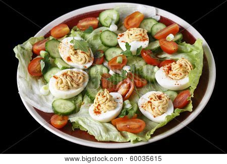 Closeup view of a salad of deviled eggs served with lettuce, miniature tomatoes, sliced cucumber and chopped green onions or scallions