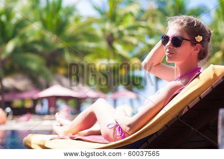 Happy young woman in bikini laying on chaise-longue luxury pool side