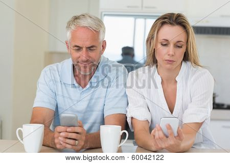 Distant couple sitting at the counter texting and not talking at home in the kitchen