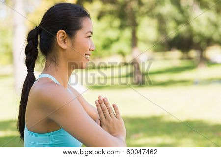 Side view of a sporty young woman in Namaste position at the park