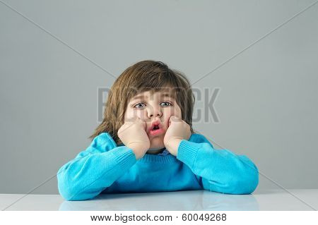 beautiful kid feeling bored isolated on grey background