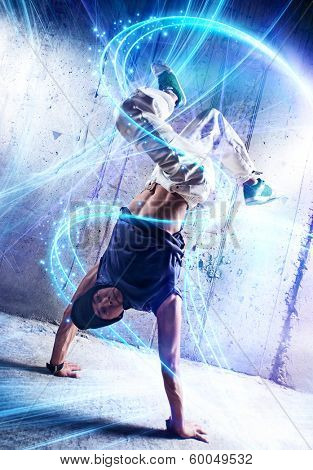 Young man break danceing on wall background.