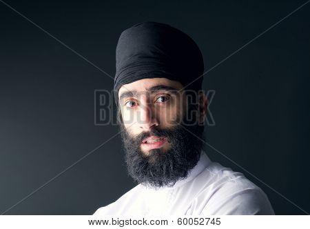 arabian muslim man wearing black scarf looking at the camera
