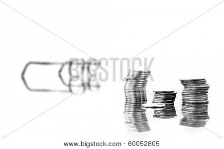 Several stacks of coins isolated on white background with reflections