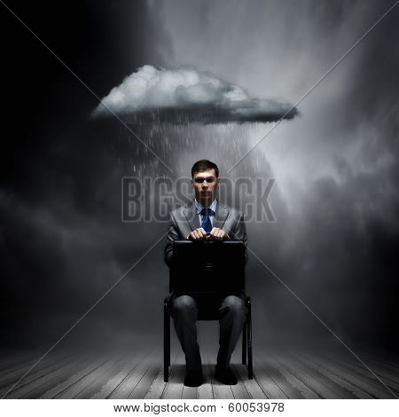 Young businessman sitting on chair with suitcase on knees