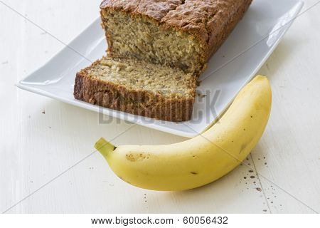 A banana and a platter with a loaf of homemade banana bread.