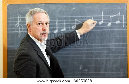 Music teacher writing notes on a blackboard