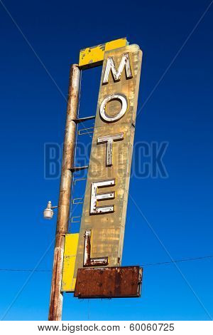 A vintage, neon, decrepit motel sign with a sky background