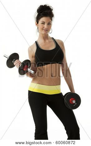 Studio photo of pretty woman standing, holding dumbbells against white background