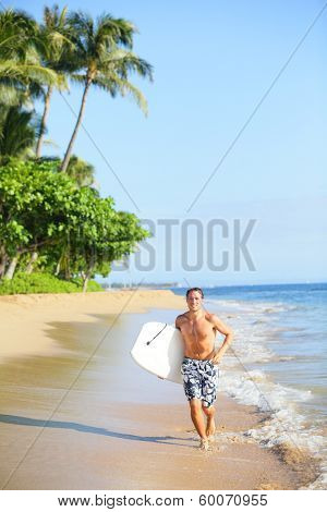Beach lifestyle man surfer with surfing bodyboard running in water on tropical beach. Handsome male model in swimwear having summer vacation holidays fun on Kaanapali beach, Maui, Hawaii, USA.